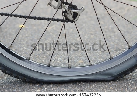 bicycle flat tire on road - stock photo
