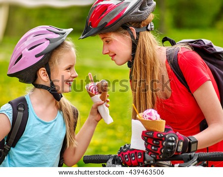 bicycle girls. Happy bicycle girls eating ice cream cone .Girls wearing bicycle helmet and gloves with rucksack rides bicycle. Children are bicycling in summer park. - stock photo