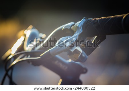 Bicycle handlebar close up, brake in focus with vignette - stock photo