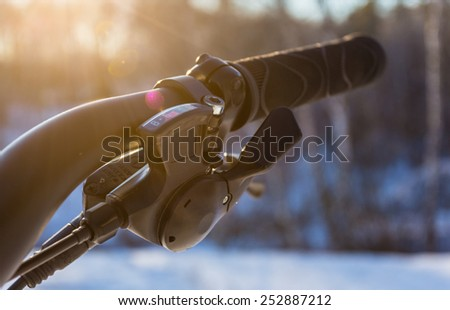 Bicycle handlebar grips and speed shifter closeup at sunset with lens flares