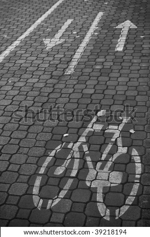 Bicycle lane road marks on cobbled  road in the city park - stock photo