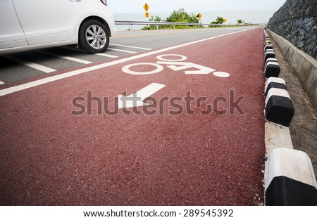 Bicycle lane with car moving pass. - stock photo
