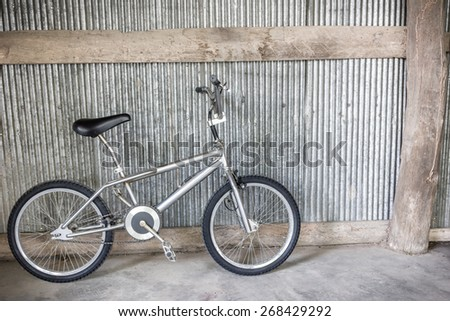 bicycle lean to the old metal sheet wall in old garage - stock photo