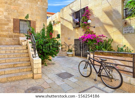 Bicycle on narrow street among typical stoned houses of jewish quarter in Old City of Jerusalem, Israel. - stock photo