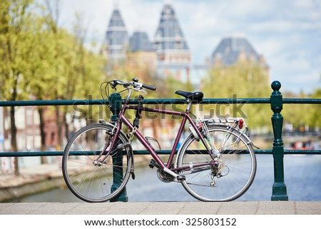 bicycle on the city street river channel bridge in Amsterdam - stock photo