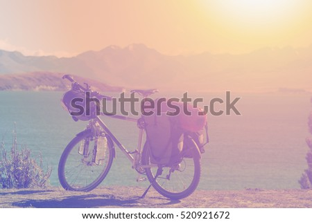 bicycle over the lake and mountains landscape at sunset