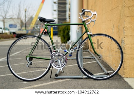 bicycle parked next to a wall with a lock on it - stock photo