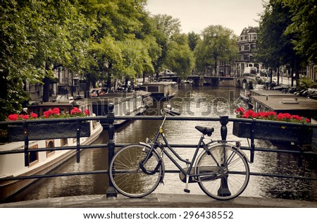 Bicycle  parked on the bridge overlooking a Canal in Amsterdam, toned with vintage brown filter. - stock photo