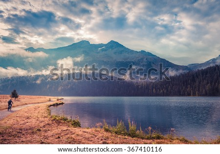 Bicycle path around Champfer lake in the Swiss Alps. Foggy summer morning on the Champferersee lake. Silvaplana town square, district of Maloja, Swiss canton of Graubunden, Switzerland, Alps, Europe. - stock photo