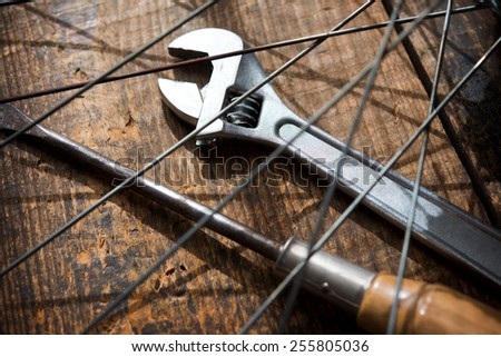 Bicycle repair. A monkey wrench and a screw driver beneath a bicycle wheel spokes. Focus is on wrench turn wheel knob. - stock photo
