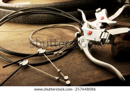 Bicycle repair. Repairing or changing a brake levers and wires of an vintage bicycle. Old bicycle wheels, brake levers, and brake wires on a grungy work desk. - stock photo
