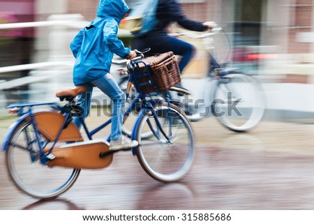bicycle rider at a rainy day in the city in motion blur - stock photo
