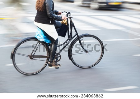 bicycle rider in a Dutch city in motion blur - stock photo