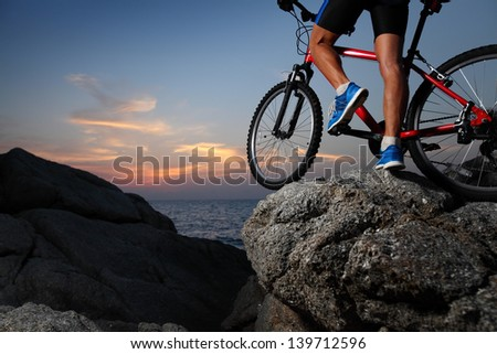 Bicycle rider standing on a rock at sunset