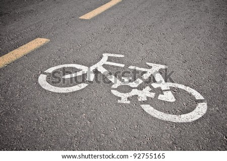 Bicycle road sign painted on the asphalt - stock photo