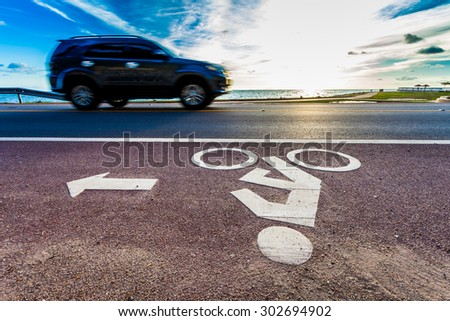 Bicycle road sign with motion blur of car and seascape in sunset - stock photo