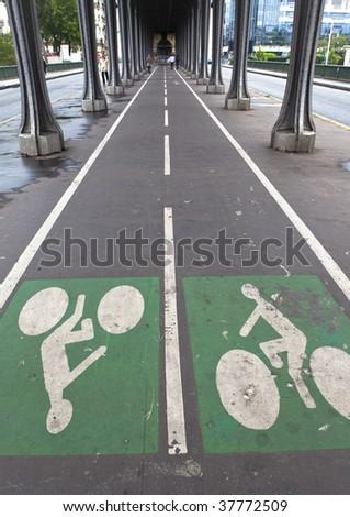 Bicycle road under transport bridge - stock photo