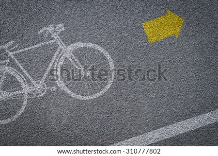 Bicycle sign on bicycle lane in asphalt road - stock photo