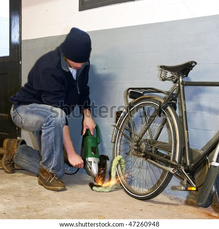 Bicycle thief busy breaking the lock with a portable grinding machine - stock photo