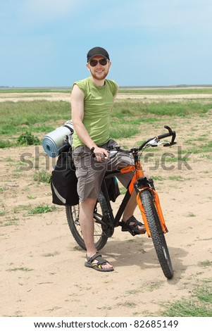 bicycle tourist standing on road and smiling, blue sky and horizon