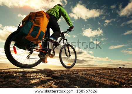 Bicycle tourist with loaded bike riding on an empty road - stock photo