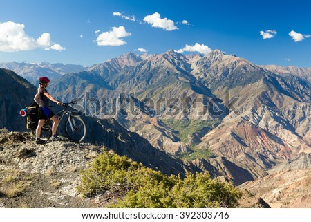 Bicycle traveler standing at cliff and enjoying mountain view - stock photo