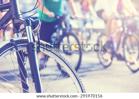 bicycle wheel detail with blurry cyclist with sunny color effect - stock photo