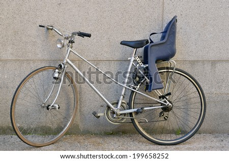 Bicycle with a baby seat parked on a wall - stock photo