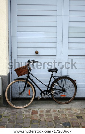 Bicycle with basket leaning against light blue door, Lille, France - stock photo