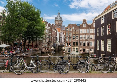 Bicycles on a bridge over the canals of Amsterdam in a summer day - stock photo