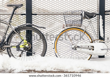 Bicycles on the street against to wire in winter. Snow Concept