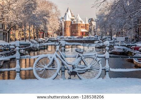 Bicycles under the Snow, view on Nieuwmarkt, Amsterdam Channels - stock photo