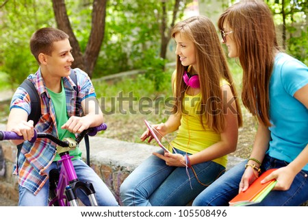 Bicycling boy meeting his female classmates in park