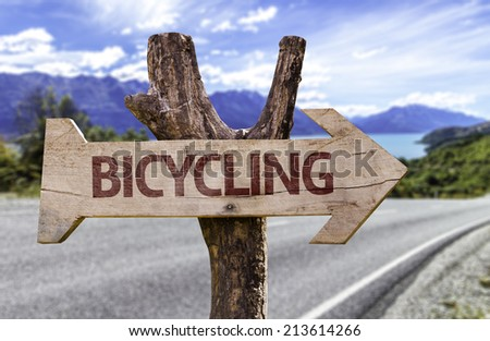 Bicycling wooden sign with a street background  - stock photo