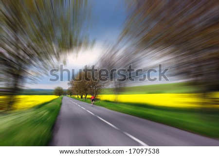 Bicyclist in red driving on rural road in Slovakia - stock photo