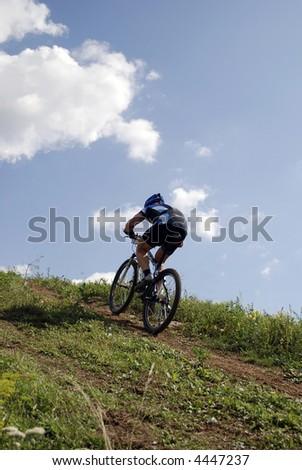 Bicyclist on a background blue sky2 - stock photo