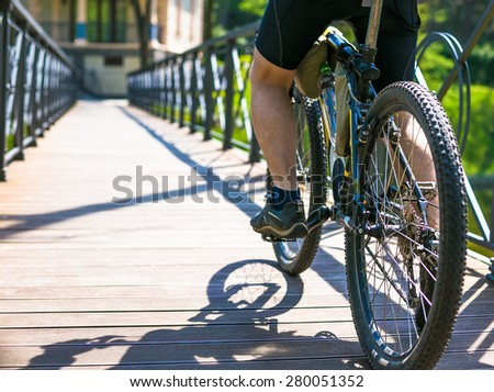 Bicyclist rides on the road in city park - stock photo