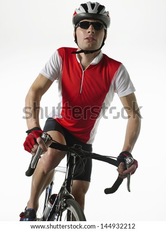 Bicyclist riding bicycle against white background - stock photo