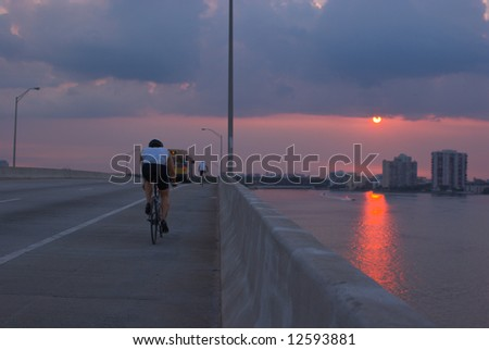 Bicyclists and Traffic on Miami Bridge at Sunset