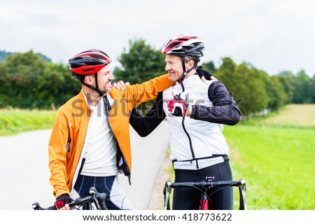 Bicyclists doing fitness sport embrace each other in finish, celebrate victory - stock photo