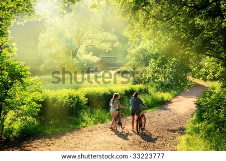 Bicyclists walk in the park with their bikes - stock photo