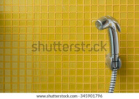 bidet shower, bidet spray in toilet with yellow tile wall