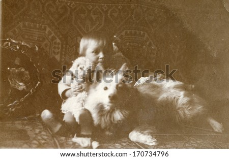 BIELSKO, POLAND, CIRCA FORTIES - vintage photo of baby with a dog and a doll