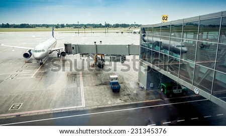 Big airliner parked next to boarding gate in airport terminal - stock photo