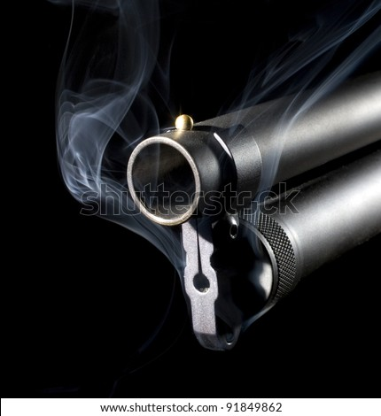 Big and black shotgun that has blue smoke near its muzzle - stock photo