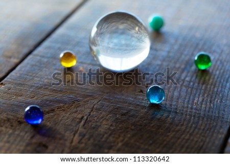Big and small marble or glass spheres on a old desk, resembling a planetary  formation. - stock photo