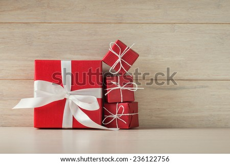 Big and small red gift boxes on wooden background - stock photo