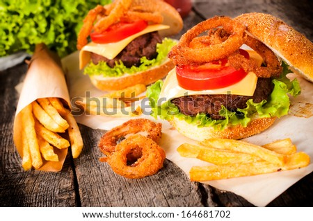 Big and tasty beef burger with onion rings and french fries.Selective focus on the burger  - stock photo