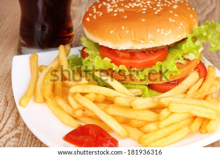 Big and tasty hamburger and fried potatoes on plate with cola close-up on wooden table