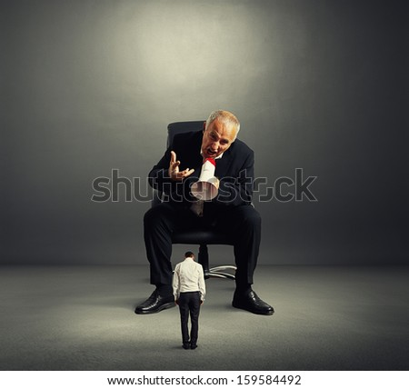 big angry boss screaming at small bad worker - stock photo